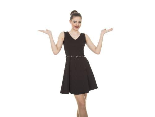 Kobieta w czarnej sukience wznosi ręce w celu zaprezentowania czegoś