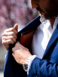 Mężczyzna wkłada do kieszeni marynarki portfel