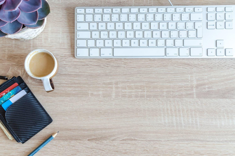 portfel i klawiatura leżą na blacie biurka