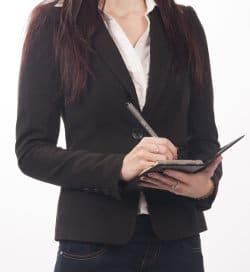 Kobieta w garniturze coś notuje