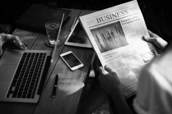Kobieta siedzi przy stoliku i czyta gazetę o biznesie