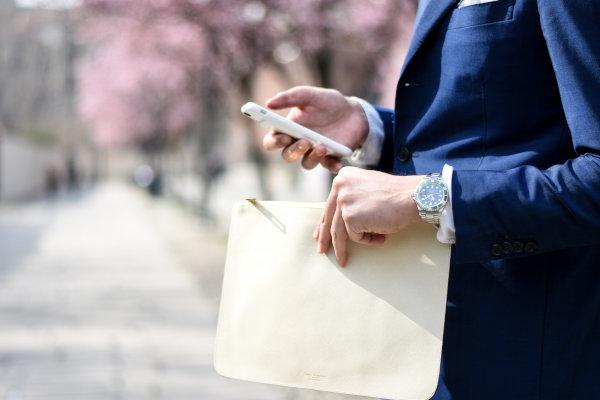 Kobieta z torebka trzyma w dłoni telefon komórkowy