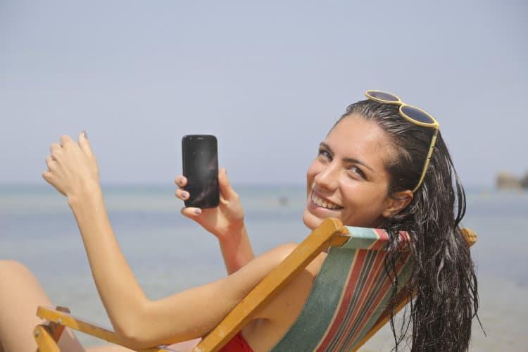 Kobieta siedzi na plażowym leżaku z telefonem komórkowym