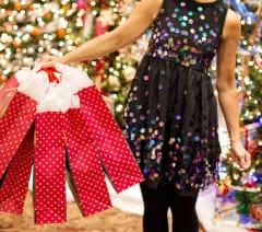 Kobieta trzyma w dłoni prezenty w torbach
